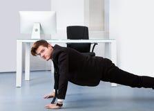 Businessman doing pushups Stock Photography