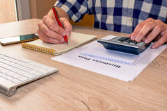 A businessman doing some paperwork using his calculator. Busines stock photos