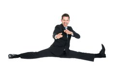Businessman doing splits while gesturing over white background Royalty Free Stock Photos