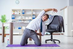 The businessman doing sports at his office space. Businessman doing sports at his office space stock images
