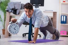 The businessman doing sports in office during break. Businessman doing sports in office during break Royalty Free Stock Photo