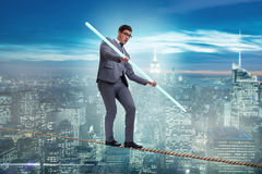 The businessman doing tightrope walking in risk concept Stock Photos
