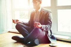 Businessman doing yoga in lotus pose stock photography