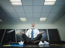 Businessman doing yoga in office Stock Photos