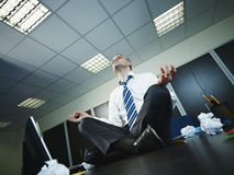 Businessman doing yoga in office Royalty Free Stock Photo