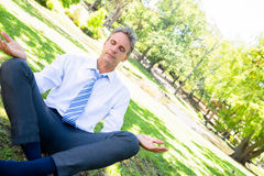 Businessman doing yoga in park Stock Photos