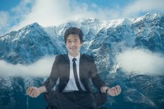 Businessman doing yoga position in front of snow-covered mountains Royalty Free Stock Images