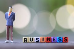 Businessman doll standing beside textbox of Business. Royalty Free Stock Photos