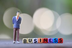 Businessman doll standing beside textbox of Business. Royalty Free Stock Photo