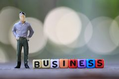 Businessman doll standing beside textbox of Business. Stock Image