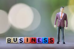 Businessman doll standing beside textbox of Business. Businessman doll standing beside textbox of Business in concept of advertising publicity Royalty Free Stock Photo