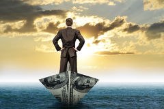 Businessman in dollar boat Stock Images