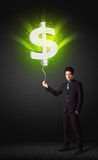 Businessman with a dollar sign balloon. Businessman holding a shining, green dollar sign balloon Royalty Free Stock Photography