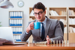 The businessman with dominoes in the office Stock Photos
