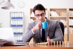 The businessman with dominoes in the office Royalty Free Stock Photography