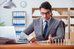 The businessman with dominoes in the office Royalty Free Stock Image