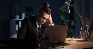 Businessman dozing off while working late night in office. African american businessman dozing off while working on laptop late night in office stock video footage
