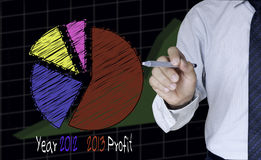Businessman draw colorful graph for year 2012-2013. Illustration of Businessman draw colorful graph for year 2012-2013 Royalty Free Stock Image