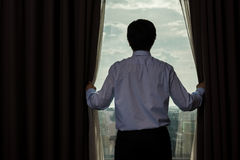 Businessman draw the curtain. Rear view of Asian businessman draw the curtain in office Stock Image