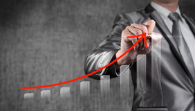Businessman draw red curve with bar chart, business strategy Royalty Free Stock Images