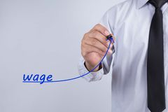 Businessman draw wage word with graph up. Business concept. stock photo