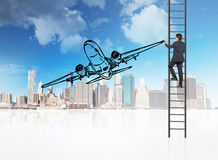 Businessman drawing airliner. Businessman standing on ladder and drawing airliner Royalty Free Stock Image