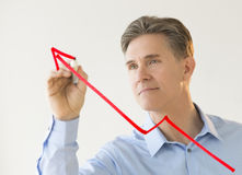 Businessman Drawing Arrow Moving Upwards On Transparent Board Stock Photo