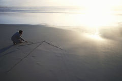 Businessman Drawing Arrow In Sand. Full length of businessman drawing arrow in sand on beach Stock Photography