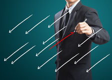 Businessman drawing arrows in different directions Royalty Free Stock Photography