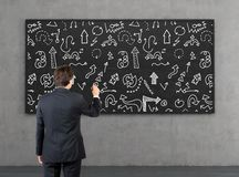 Businessman drawing arrows. Young businessman drawing arrows on blackboard Royalty Free Stock Photo
