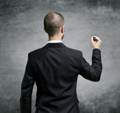 Businessman drawing. Businessman back turned, draws on a transparent surface Stock Images