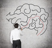 Businessman drawing brain. On a concrete wall Royalty Free Stock Image