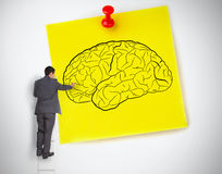 Businessman drawing a brain on a giant post it. On white background stock photography