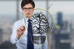Businessman drawing brain lamp. On invisible screen Royalty Free Stock Photo