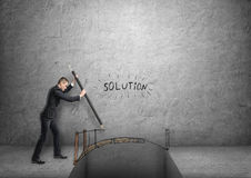 Businessman drawing bridge over gap with word 'solution' above it Stock Photos