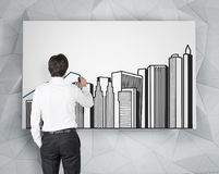 Businessman drawing buildings Royalty Free Stock Photo