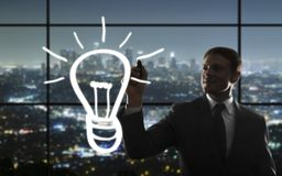 Businessman drawing bulb Stock Photo