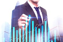 Economy and sales concept. Businessman drawing business chart on abstract city background. Economy and sales concept. Double exposure Stock Image