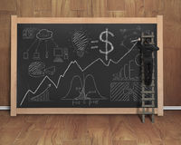 Businessman drawing business concept doodles on black chalkboard Stock Photos