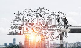 Businessman drawing business conceptual sketches. Businessman in suit drawing business-analytical strategy while standing on broken bridge with cityscape and Royalty Free Stock Images