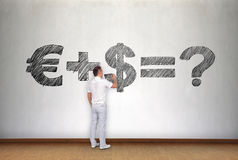 Businessman drawing business formula. Young businessman drawing business formula on wall Stock Images