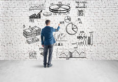 Businessman drawing business plan, graph, chart on Stock Photo
