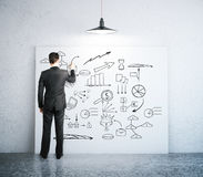 Businessman drawing business sketch. On whiteboard in leaning on wall in concrete room Stock Photography