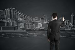 Businessman drawing city. Back view of young businessman drawing city on gray wall. Art concept stock photography
