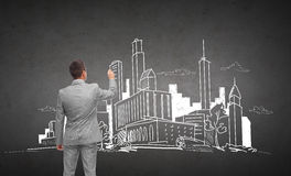 Businessman drawing city sketch from back. Business, people, architecture and real estate concept - businessman drawing city sketch from back over dark gray royalty free stock photos