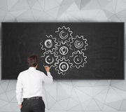 Businessman drawing cog Stock Images