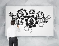 Businessman drawing cogs Stock Photo