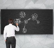 Businessman drawing cogs Stock Photography