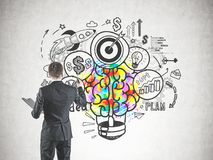Businessman drawing creative idea sketch. Rear view of a young successful businessman drawing creative and bright business start up idea icons on a concrete wall Royalty Free Stock Image