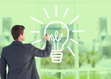 Businessman drawing electric bulb against office window background Stock Photos